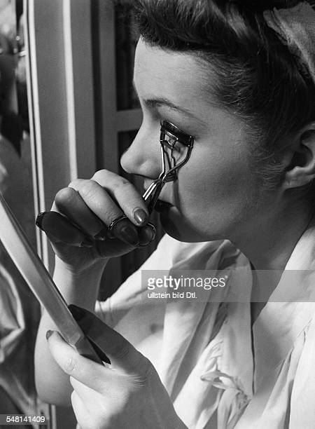 Model at a photo shooting session curling her eyelashs with an eyelash curler 1941 Photographer Regine Relang Published by 'Signal' 10/1941 Vintage...