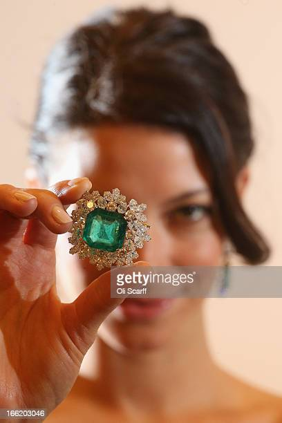 Model at Sotheby's auction house holds an emerald and diamond broach from the collection of actress Gina Lollobrigida, which is expected to fetch...
