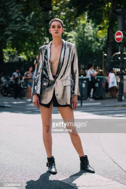 Model Ava McAvoy wears pink sunglasses and a silver flashy Each x Other blazer and black boots after Jean Paul Gaultier during Couture Fall/Winter...