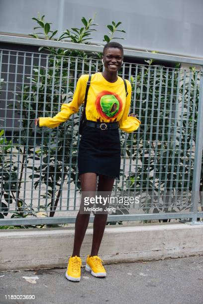 Model Awar Mou wears Airpods a yellow Alien shirt black skirt and yellow Fila sneakers after the Fila show during Milan Fashion Week Spring/Summer...