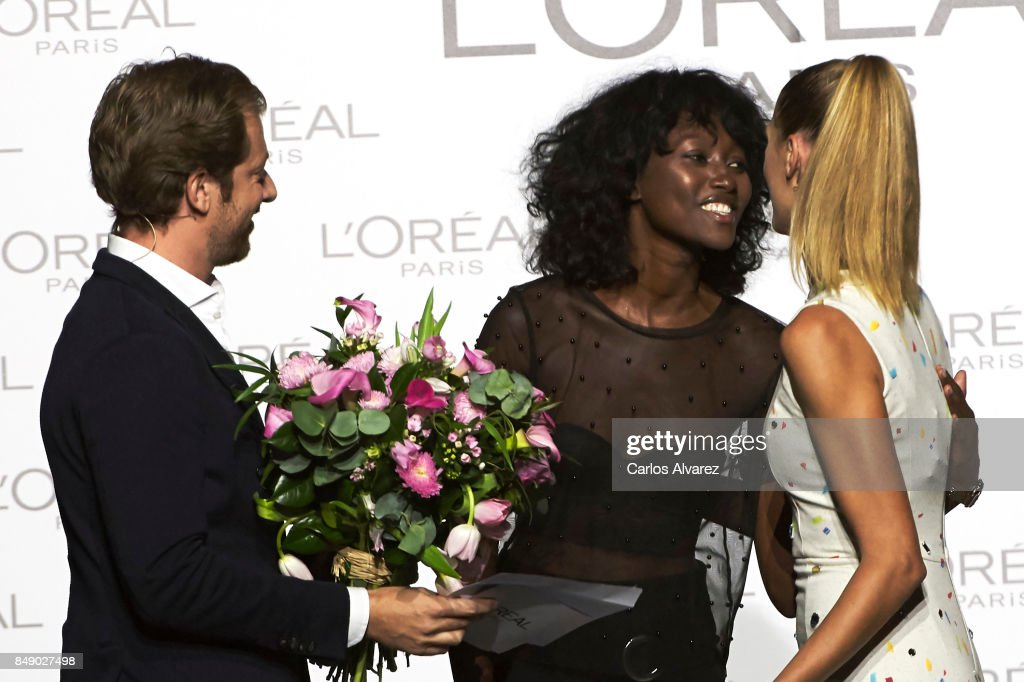 Model Aya Gueye (C) receives the L'Oreal Paris Award from L'Oreal Paris Brand General Manager Gregory Recoing (L) and Spanish model Laura Sanchez (R) during the Mercedes-Benz Fashion Week Madrid Spring/Summer 2018 at Ifema on September 18, 2017 in Madrid, Spain.