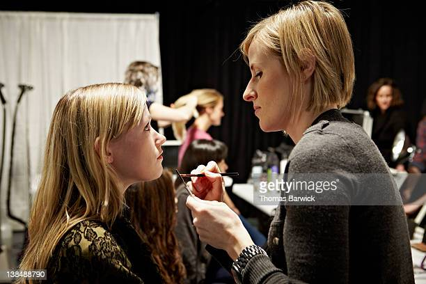 Model backstage at fashion show in make-up