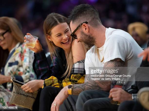 Model Behati Prinsloo and her husband singer Adam Levine share a laugh during the Lakers' home opener against the Houston Rockets at Staples Center...