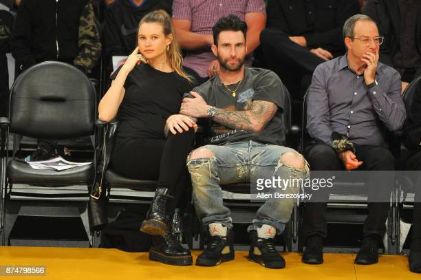 Model Behati Prinsloo and singer Adam Levine attend a basketball game between the Los Angeles Lakers and the Philadelphia 76ers at Staples Center on...