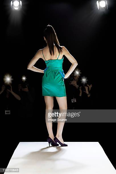 model being photographed on catwalk at fashion show - green dress stock pictures, royalty-free photos & images