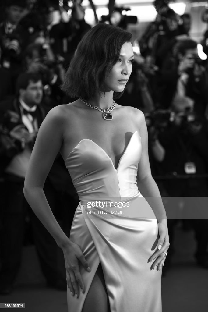 US model Bella Hadid poses as she arrives on May 17, 2017 for the screening of the film 'Ismael's Ghosts' (Les Fantomes d'Ismael) during the opening ceremony of the 70th edition of the Cannes Film Festival in Cannes, southern France. / AFP PHOTO / Alberto PIZZOLI