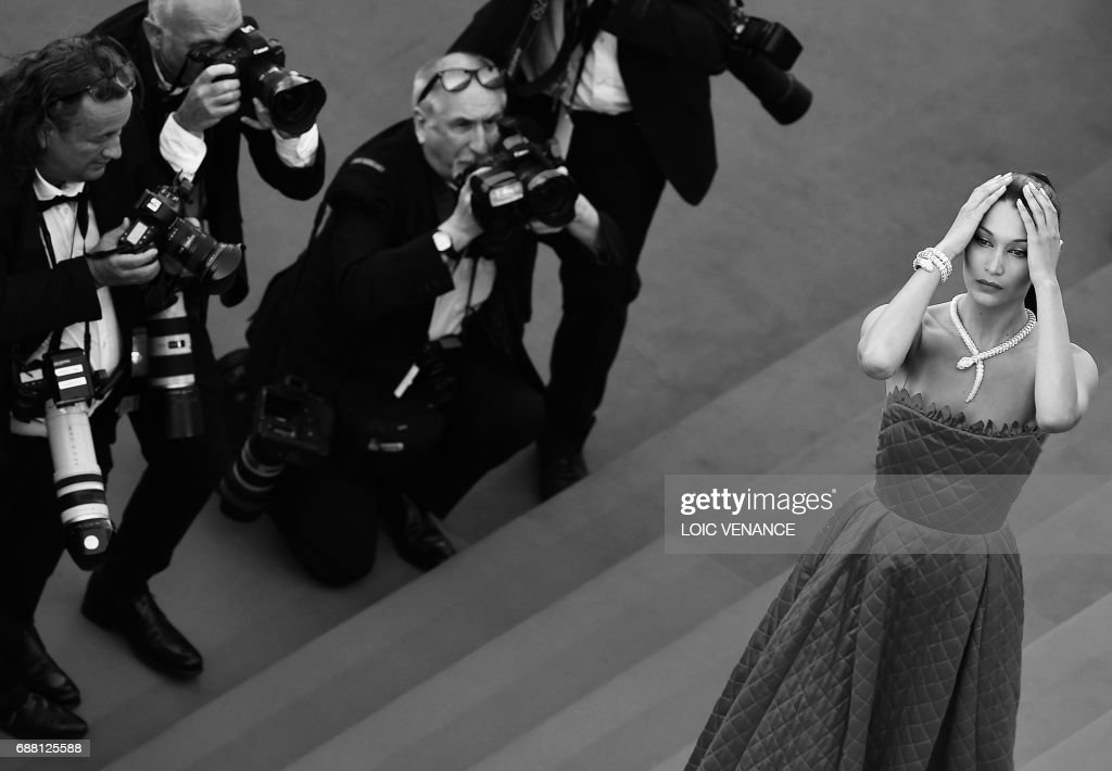 US model Bella Hadid poses as she arrives on May 19, 2017 for the screening of the film 'Okja' at the 70th edition of the Cannes Film Festival in Cannes, southern France. /
