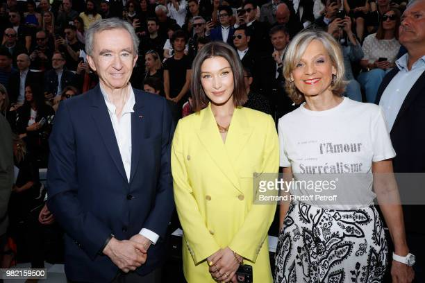 Model Bella Hadid standing between Owner of LVMH Luxury Group Bernard Arnault and his wife Helene Arnault attend the Dior Homme Menswear...