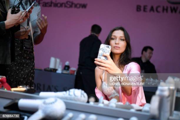 US model Bella Hadid takes a selfie as she gets ready backstage before the Victoria's Secret fashion show at the Grand Palais in Paris on November 30...