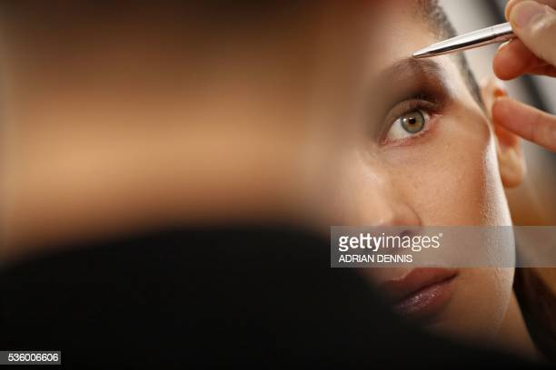 Model Bella Hadid waits as a make-up artist applies finishing touches to her eyebrow backstage ahead of the Christian Dior Cruise fashion show at...