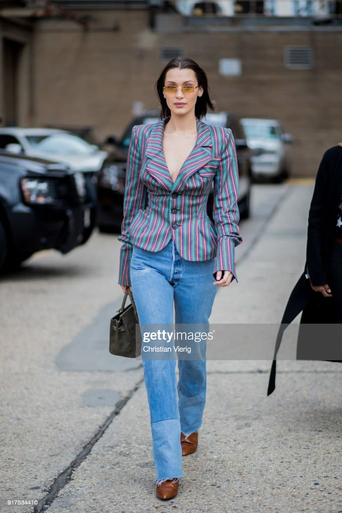Model Bella Hadid wearing denim jeans, striped blazer jeans, sunglasses seen outside Ralph Lauren on February 12, 2018 in New York City.