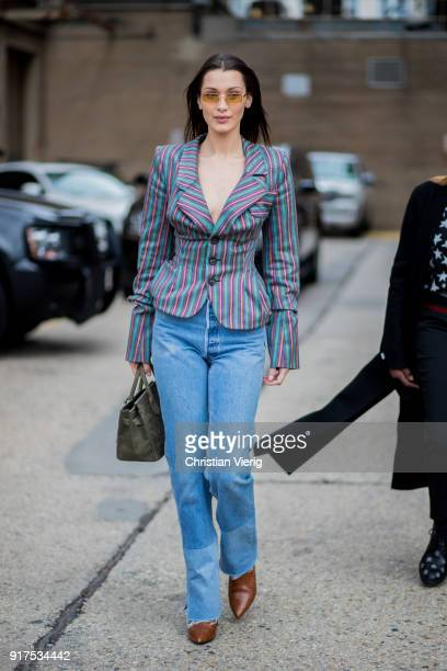 Model Bella Hadid wearing denim jeans striped blazer jeans sunglasses seen outside Ralph Lauren on February 12 2018 in New York City