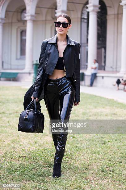 Model Bella Hadid wears an all black outfit including a cropped leather jacket crop/bra top and latex pants outside the Alberta Ferretti show during...