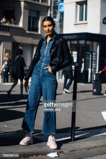 Model Bella Newman wears a cropped black leather jacket a denim jumpsuit and light pink Fila sneakers after the Y/Project show during Paris Fashion...