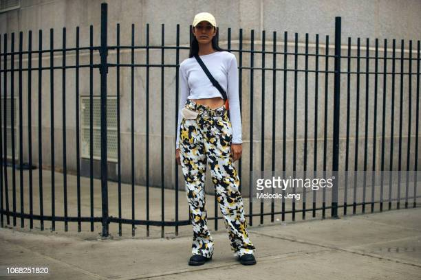 Model Bella Newman wears a yellow cap cropped white longsleeve shirt yellow splatter paint pants and black boots after the 31 Phillip Lim show during...