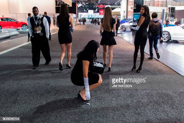 A model bends down to pick up candy she dropped as she and other models walk through the 2018 North American International Auto Show in Detroit...