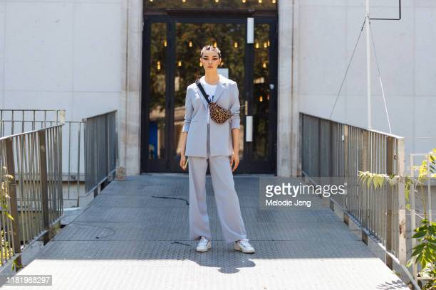 Model BingBing Liu wears a gray suit, white sneakers, and leopard fanny pack after the Elie Saab show during Couture Fashion Week Fall/Winter 2019 on...