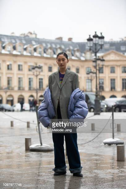 Model BingBing Yuan wears a purple puffer jacket off her shoulders gray blazer and oversized jeans after the Alexis Mabille show during Couture...