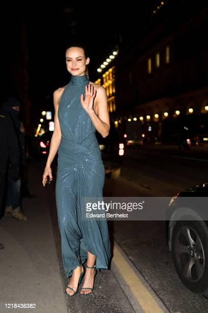 Model Birgit Kos wears a turtleneck sleeveless blue turtleneck glittering dress, shoes, the Harper's Bazaar Exhibition as part of the Paris Fashion...