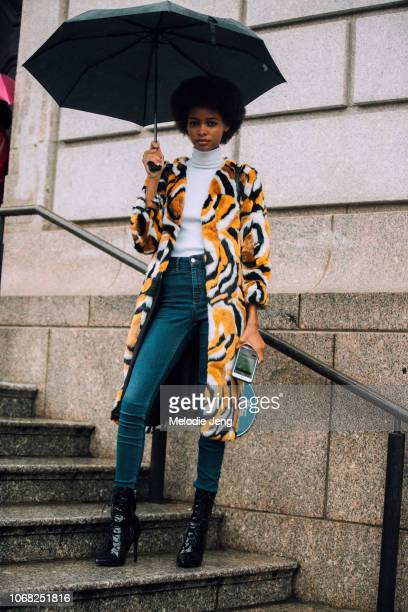 Model Blesnya Minher holds and umbrella and wears a yellow fur coat white turtleneck blue jeans and black highheeled boots after the Carolina Herrera...