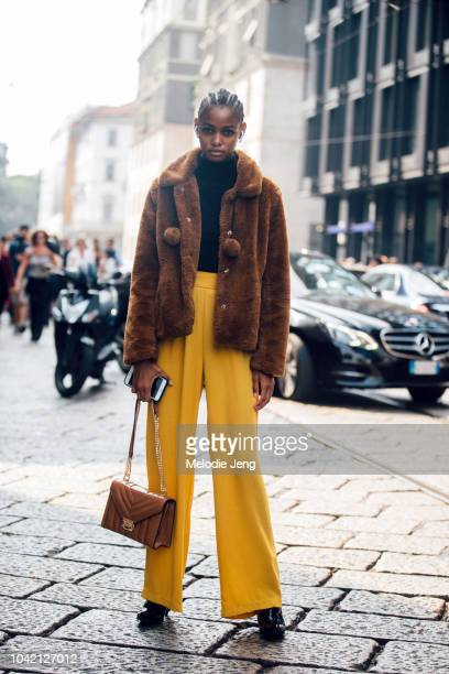 Model Blesnya Minher in a brown cropped teddy bear coat orange pants brown leather purse after Sportmax during Milan Fashion Week Spring/Summer 2019...