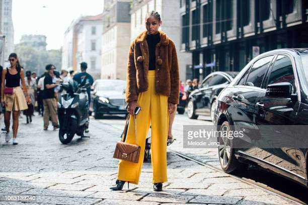 Model Blesnya Minher wears a brown teddy bear jacket black top yellow loose pants light brown leather purse and black heels during Milan Fashion Week...