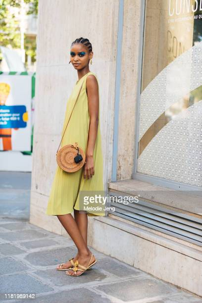 Model Blesnya Minher wears a green pleated sleeveless dress, round woven bag, and woven sandals after the Valentino show during Couture Fashion Week...