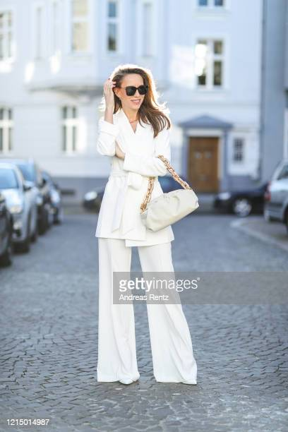 Model Blogger and Influencer Alexandra Lapp is seen wearing a white suit from Alice Olivia The Chain Pouch from Bottega Veneta in white leather with...