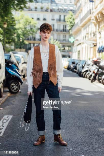 Model Bo Gebruers wears a brown suede fringe vest, white top, blue jeans, and brown boots after the Jean Paul Gaultier show during Couture Fashion...