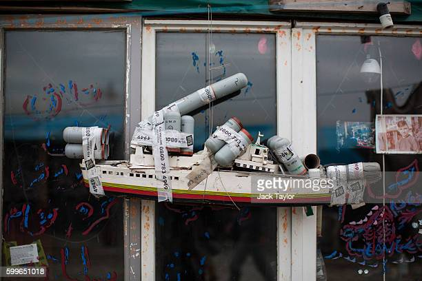 A model boat decorated with tear gas canisters hangs outside a shop window near to the Jungle Books Cafe at the Jungle migrant camp on September 6...