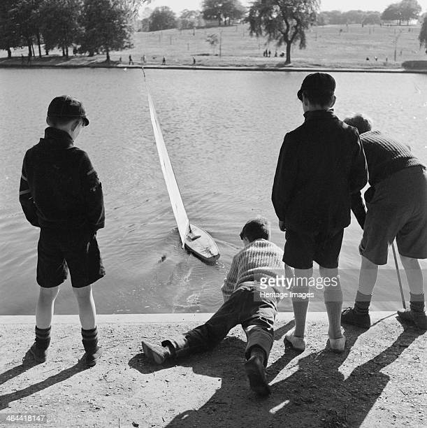 Model boating lake near Parliament Hill Hampstead Heath London c1960c1965 Three boys standing watching a model yacht being launched by a fourth boy...