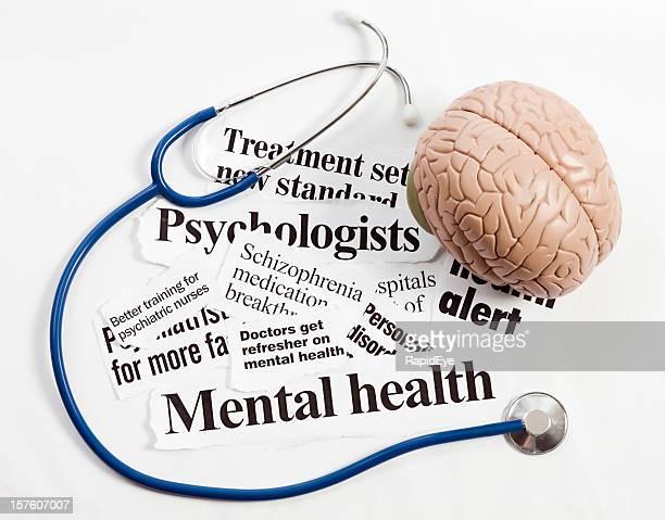 Model brain and stethoscope sit on mental health headlines