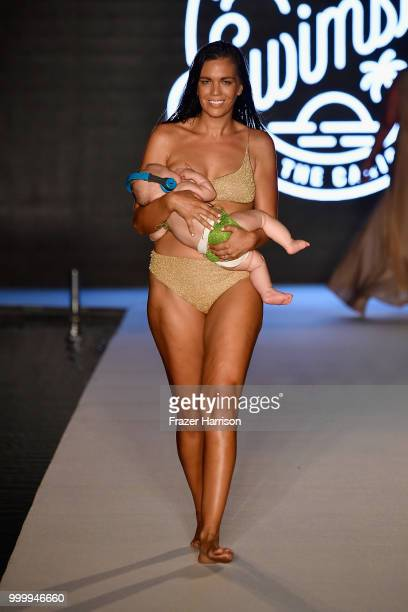 A model breastfeeds while walking the runway for the 2018 Sports Illustrated Swimsuit show at PARAISO during Miami Swim Week at The W Hotel South...