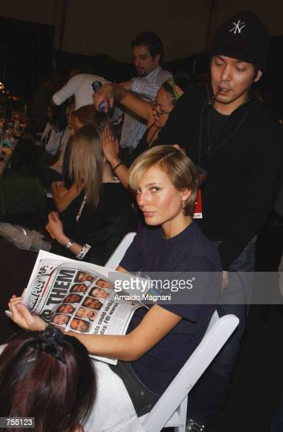 Model Brigitte Hall reads the New York Post as her is styled for the Luca Luca Fashion Show February 12 2002 in New York City