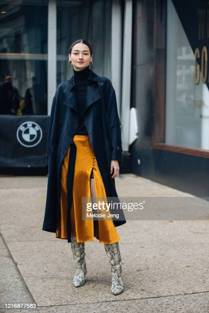 Model Bruna Tenorio wears a black trench coat, orange pleated skirt, and white python boots after the Jonathan Simkhai show on February 10, 2020 in...