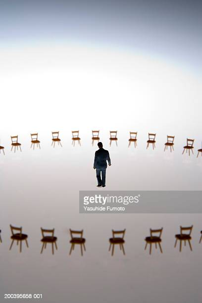 Model businessman in center of circle of miniature chairs, rear view