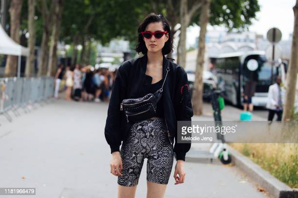 Model Cami YouTen wears red triangular sunglasses a black Marc Jacobs jacket black fanny pack and python biker shorts after the Kenzo show during...