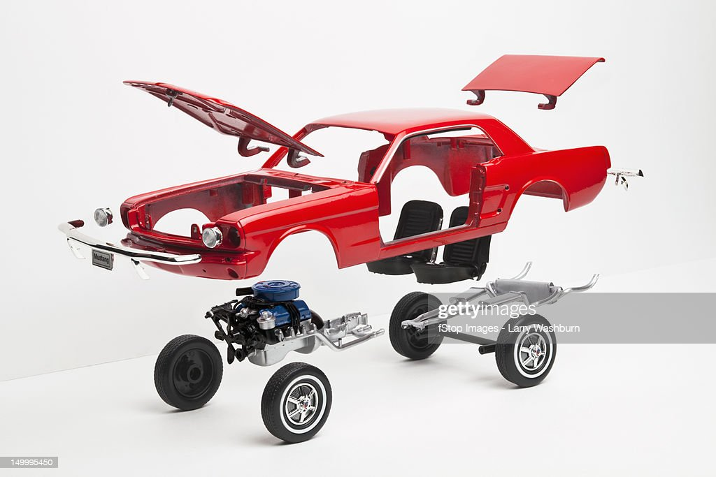 A model car taking a part, some pieces in mid-air : Stock Photo