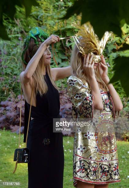 Model Cara Delevingne adjusts the mask worn by sister Poppy Delevingne as they attend a reception hosted by Prince Charles Prince of Wales and...