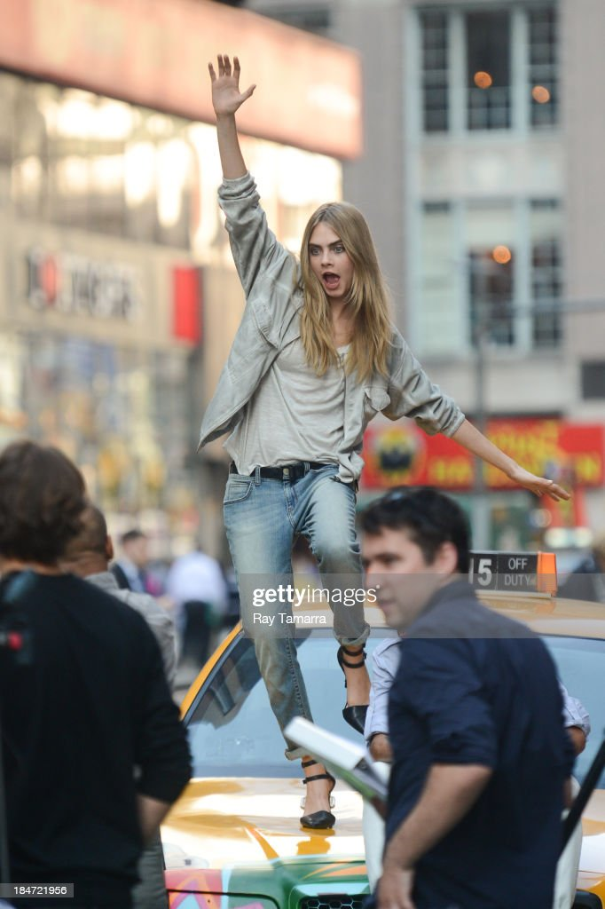 Model Cara Delevingne poses for photos at a DKNY photo shoot in Times Square on October 15, 2013 in New York City.