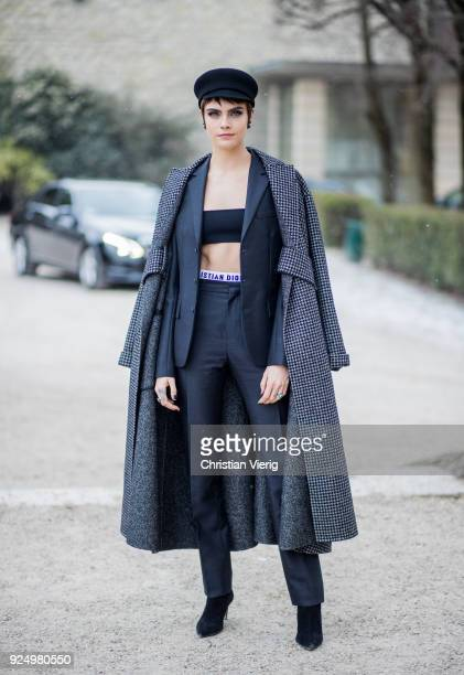 Model Cara Delevingne wearing a cropped top navy pants military hat grey wool coat is seen outside Dior on February 27 2018 in Paris France