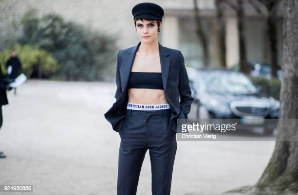 Model Cara Delevingne wearing a cropped top navy pants military hat is seen outside Dior on February 27 2018 in Paris France