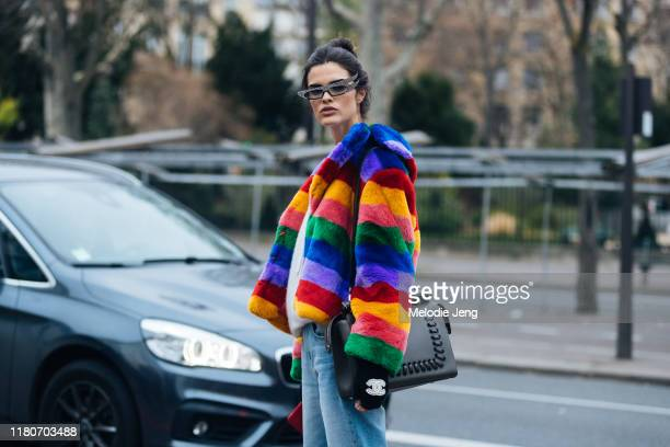Model Carol Mendes wears skinny sunglasses a rainbow fur jacket Chanel fingerless gloves after Heron Preston at Palais de Tokyo during Paris Fashion...