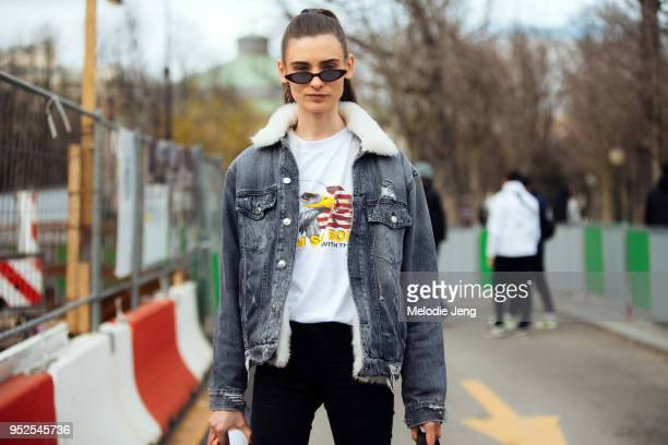 Model Carolina Thaler wears skinny sunglasses and a gray denim jacket with shearling collar on March 06 2018 in Paris France