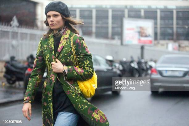 Model Caroline Brasch Nielsen exits the Dries Van Noten show in a green and yellow floral jacquard jacket black beret and yellow Chanel bag during...