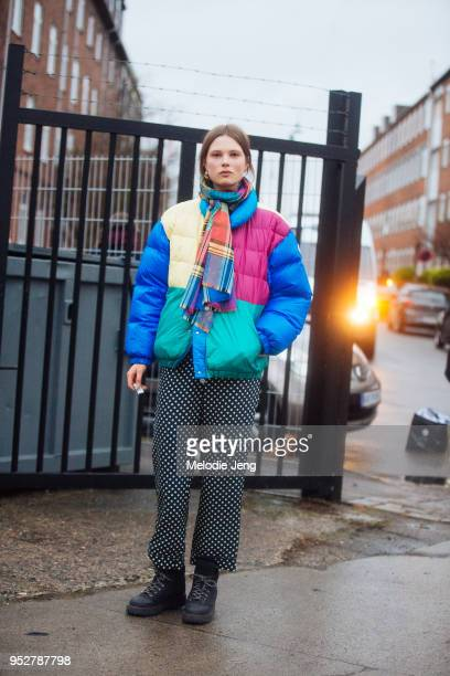 Model Caroline Brasch Nielsen wears a madras colorful scarf a multicolor down jacket black and white polka dot pants and black boot sat Copenhagen...