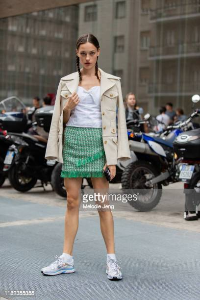 Model Caroline Knudsen wears a tan military-style jacket, white top, green tweed skirt, and white Nike sneakers outside the Max Mara show during...
