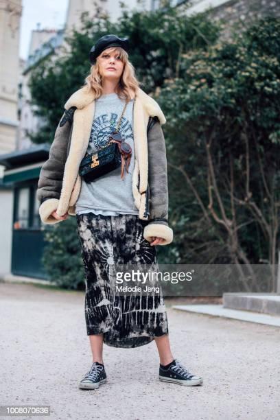Model Caroline Schurch exits the Dior show at Musee Rodin in a black beret brown shearling bomber jacket University of Alaska sweatshirt Dior purse...