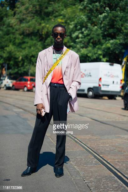 Model Cheikh Kebe wears a pink blazer, Off-White bag, Daily Paper shirt, black pants, and black boots after the Fendi show during the Milan Men's...