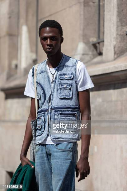 Model Cherif Douamba wears a denim vest with pockets, white t-shirt, and jeans after the Margiela show during Couture Fashion Week Fall/Winter 2019...